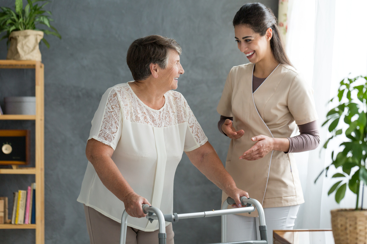 helping older woman with walker