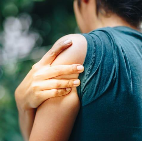 woman rubbing sore shoulder